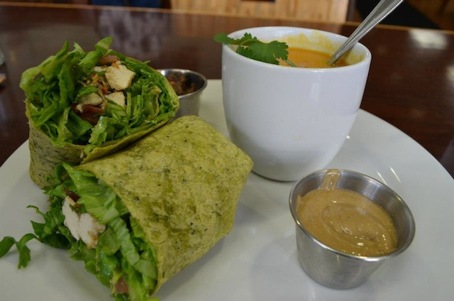 A delicious and healthy combo lunch: Sesame ginger tofu with housemade Thai peanut sauce in a whole grain spinach wrap served with a cup of carrot ginger soup.