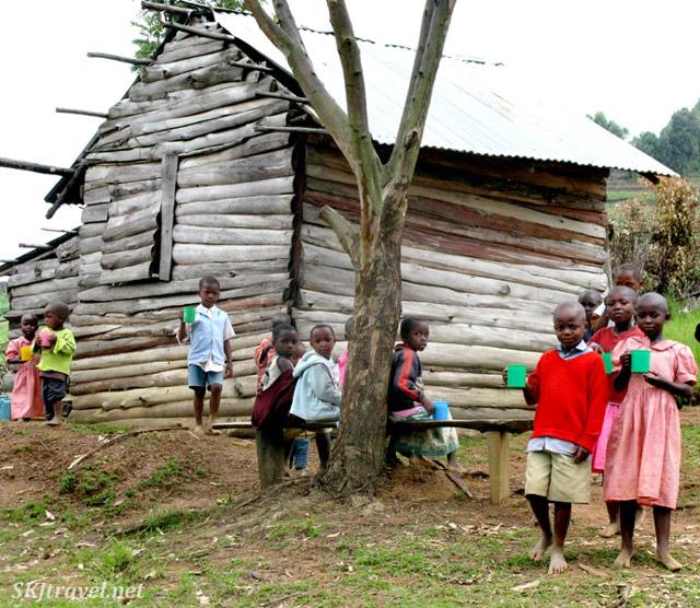 Children eating their morning porridge on the school grounds where I stayed